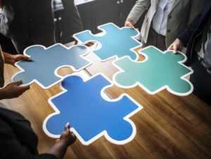 4 people holding large puzzle pieces